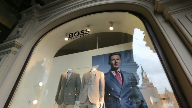 pedestrians walk past the windows of a hugo boss designer clothes store, part of the gum department store, in moscow, russia, on tuesday, june 10... - hugo boss stock-videos und b-roll-filmmaterial