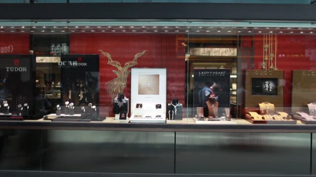 vidéos et rushes de pedestrians walk past window displays of jewelry outside a chow sang sang holdings international ltd jewelry store in the mong kok district of hong... - mong kok