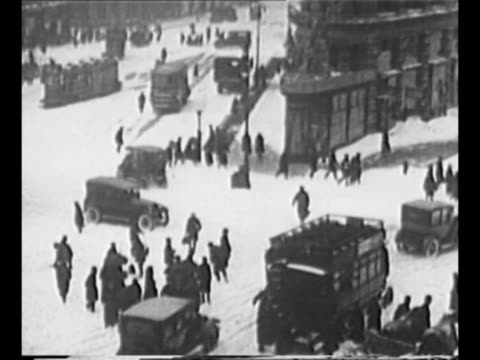 pedestrians walk slip on ice as they walk in new york city in 1920 during snowstorm / traffic and pedestrians make their way through streets filled... - 横滑り点の映像素材/bロール