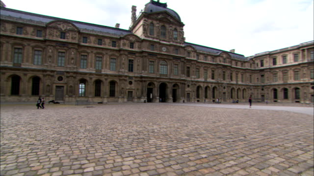 stockvideo's en b-roll-footage met pedestrians walk through a giant palace courtyard paved with cobblestones. - binnenplaats