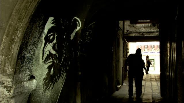 pedestrians walk through a narrow stone corridor in a venice ghetto. available in hd. - ghetto video stock e b–roll