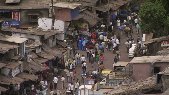 pedestrians walk through a rundown marketplace in dharavi. - slum stock-videos und b-roll-filmmaterial