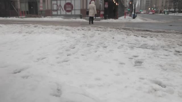 pedestrians walk through a snowcovered crosswalk in washington dc us on tuesday march 14 2017 shots close ups of slush and snow as pedestrians walk... - slush stock videos and b-roll footage