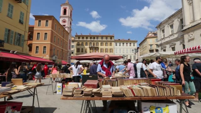 Pedestrians walk through a town square in Nice France on Thursday May 14 2015 SHOTS customers browse the book stalls of an outdoor market in the...