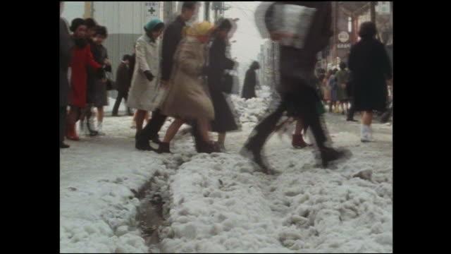 Pedestrians walk through snow covering Ginza Street.