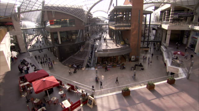 pedestrians walk through the artium of cabot circus shopping centre in bristol. available in hd. - atrio cuore video stock e b–roll