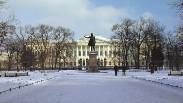 Pedestrians walk through the snow near a statue on a pedestal.