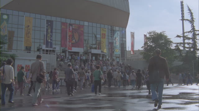 Pedestrians walk toward and enter a stadium.