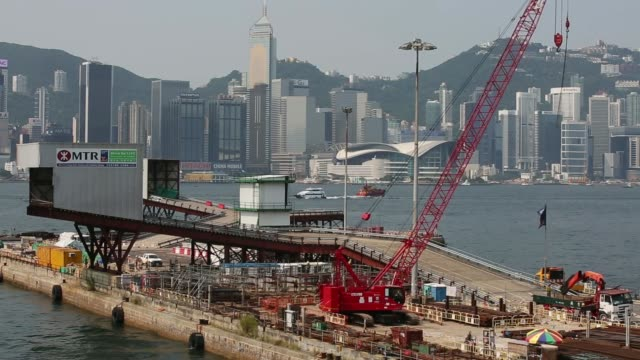 vídeos de stock, filmes e b-roll de pedestrians walk up a bridge beside a highway in the hung hom area of the kowloon city district in hong kong china a crane operates at an mtr corp... - the center