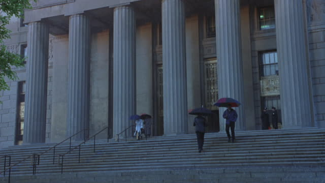 Pedestrians walk up and down the stairs of a courthouse in the rain.