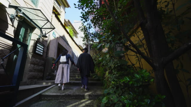pedestrians walk up the narrow stone stair alley, which alleyway is surrounded by buildings in kagurazaka tokyo.there are some restaurants and bars at both side of alleyway. - alley stock videos & royalty-free footage