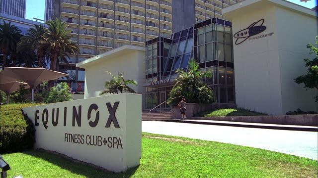 vídeos de stock, filmes e b-roll de pedestrians walk up to the entrance of the equinox fitness club and spa. - escrita ocidental