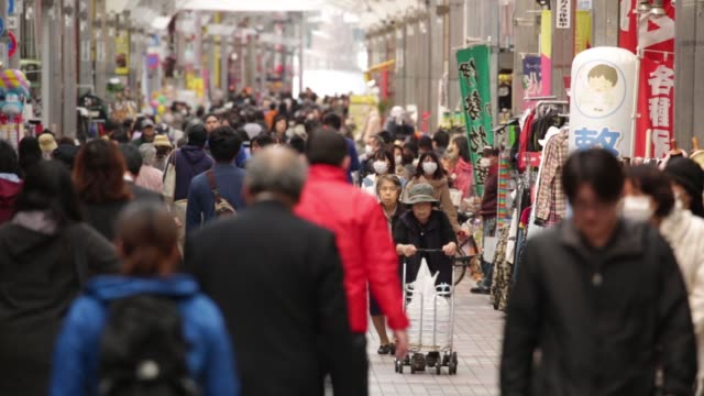 Pedestrians walk while others push their bicycles through a shopping arcade in Tokyo Japan on Monday March 23 Elderly women push their shopping carts...