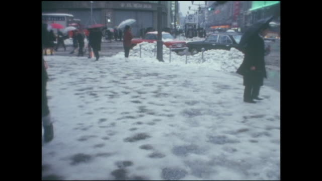 vídeos de stock, filmes e b-roll de pedestrians walk with caution over a snowy sidewalk near the ginza 4-chome intersection. - roupa quente