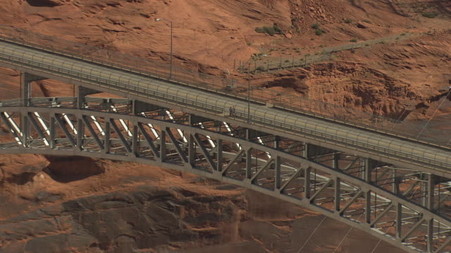 ms aerial zo pedestrians walking across bridge at glen canyon dam and surrounding landscape / arizona, united states - glen canyon staudamm stock-videos und b-roll-filmmaterial