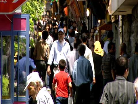 vidéos et rushes de pedestrians walking along a crowded sidewalk / tehran, iran - format vignette