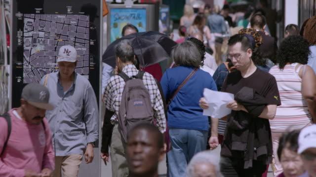 Pedestrians walking along New York City sidewalk in Chinatown on a hot summer day.