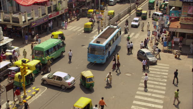 Pedestrians walking among traffic to cross busy street in New Delhi, India. Available in HD.