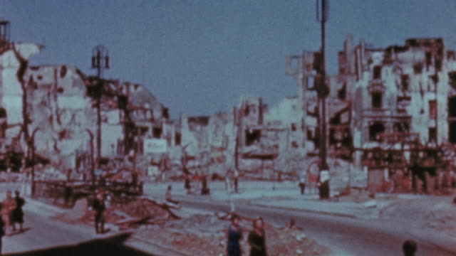 vidéos et rushes de pedestrians walking amongst the ruins of bombed out buildings / berlin germany - 1945