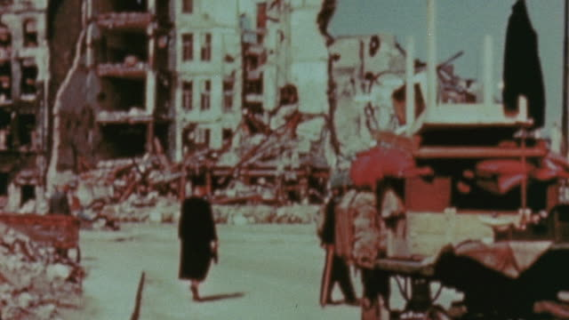 pedestrians walking amongst the ruins of bombed out buildings, refugees hauling their belongings in handcarts / berlin, germany - rubble stock videos & royalty-free footage