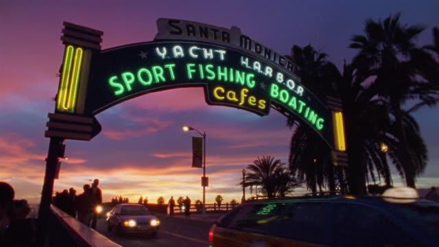 la ws pedestrians walking and traffic driving along street under santa monica yacht harbor sign at sunset / santa monica, california, usa - santa monica pier sign stock videos & royalty-free footage