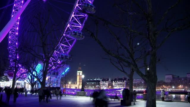 SM WS Pedestrians walking below Millennium Wheel with Big Ben in background / London, England
