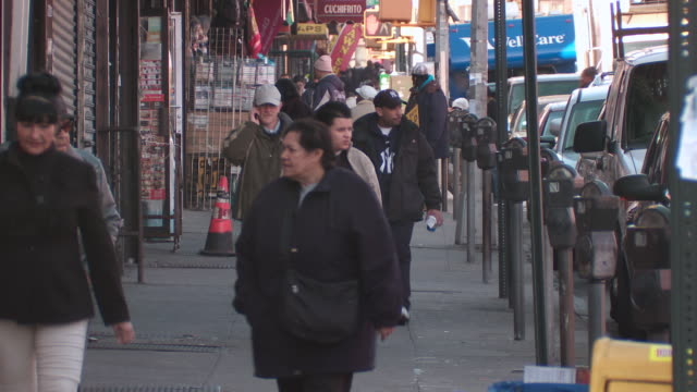 Pedestrians walking down a busy street in the bronx past parked cars, parking meters and store fronts during the day