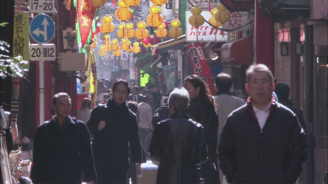 MS Pedestrians walking down a crowded, narrow street past local businesses / Yokohama, Kanagawa Prefecture, Japan
