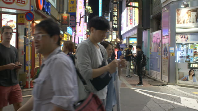 pedestrians walking down a street in tokyo, japan. - (war or terrorism or election or government or illness or news event or speech or politics or politician or conflict or military or extreme weather or business or economy) and not usa点の映像素材/bロール