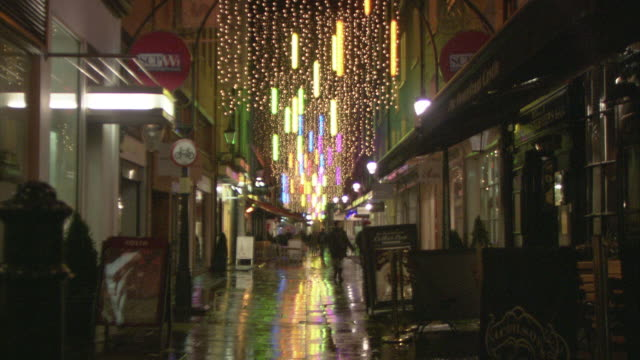 ws pedestrians walking down city alley at night / westminster, london, united kingdom - 路地点の映像素材/bロール