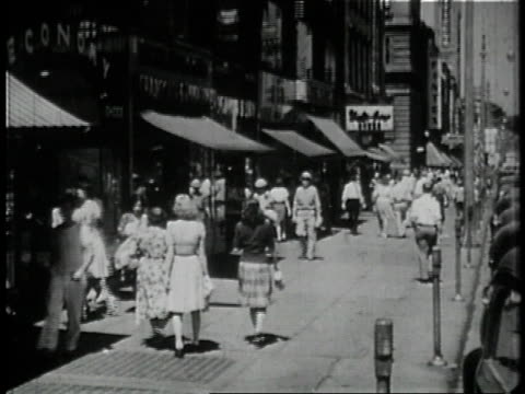 1946 montage pedestrians walking down crowded city street / ws crowds in ballpark bleachers / new york city, new york, united states - 1946年点の映像素材/bロール