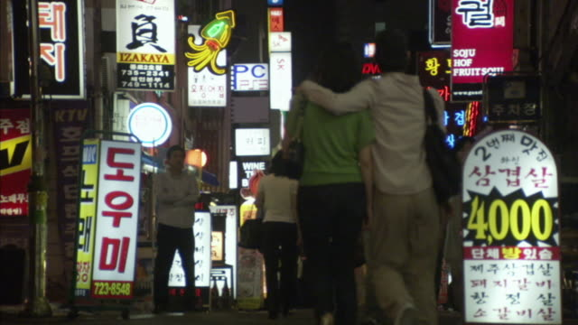 MS LA Pedestrians walking downtown street at night, car driving and stopping in front of camera, Seoul, South Korea