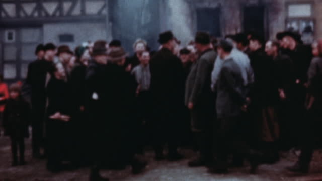 pedestrians walking gathering on streets and talking with us army soldiers smoldering and burned village buildings behind them / germany - 1945 stock-videos und b-roll-filmmaterial
