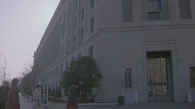 stockvideo's en b-roll-footage met pedestrians walking near the united states department of justice building. - telefooncel