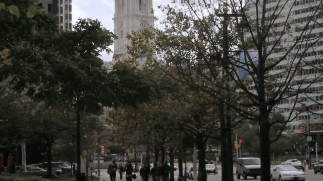 TU Pedestrians walking on a downtown street with Statue of William Penn on the city hall tower / Philadelphia, Pennsylvania, United States