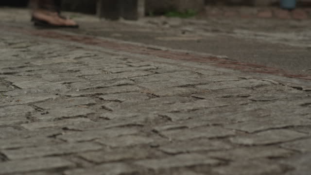 pedestrians walking on brick street - uneven stock videos & royalty-free footage