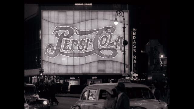 WS Pedestrians walking on city street with Pepsi Cola sign at night in Times Square / New York City, New York, United States