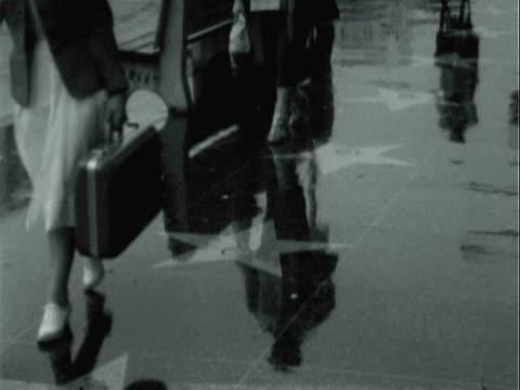 stockvideo's en b-roll-footage met montage pedestrians walking on rain-slicked sidewalks displaying celebrity brass stars / los angeles, california, united states - hollywood walk of fame