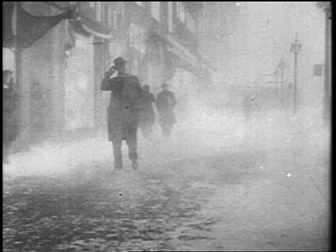 B/W 1935 pedestrians walking on sidewalk in windy snowstorm / educational
