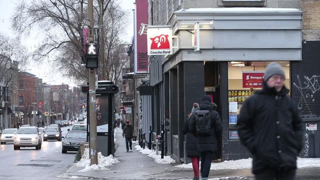 vídeos y material grabado en eventos de stock de pedestrians walking on sidewalk passing couche-tard convenience store in montreal, quebec, canada, on wednesday, january 13, 2021. - escritura occidental