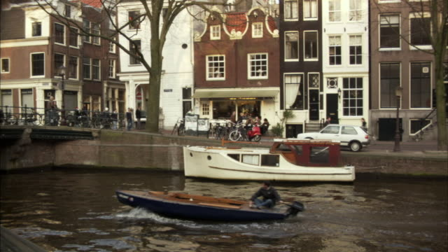 vidéos et rushes de ms, pedestrians walking on street along canal,  man in speed boat in foreground, amsterdam, netherlands - moins de 10 secondes