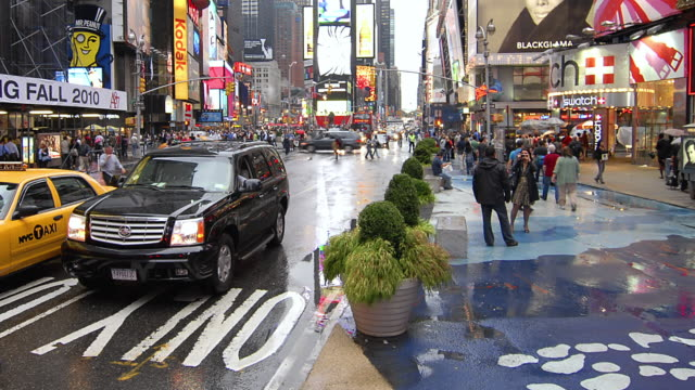 T/L Pedestrians walking on the sidewalk in Times Square next to busy street / New York City, New York, United States
