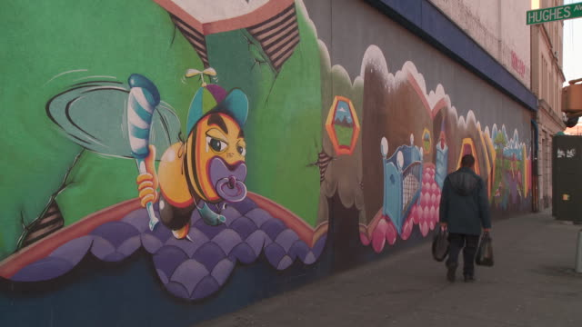 pedestrians walking past a building nearr hughes avenue in the bronx past a wall covered with beautiful, elaborate grafiti during the day - graffiti stock videos & royalty-free footage