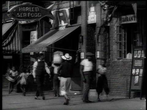 1939 WS Pedestrians walking past Harlem Seafood store / New York City, USA