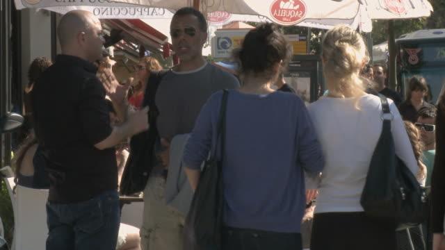 ms pedestrians walking past people in sidewalk cafe / tel aviv, israel - tel aviv stock videos & royalty-free footage