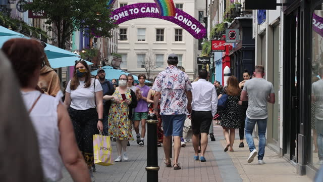 pedestrians walking past properties on carnaby street in soho owned by shaftesbury plc, who have noted an increase in demand for empty commercial... - large group of people stock videos & royalty-free footage