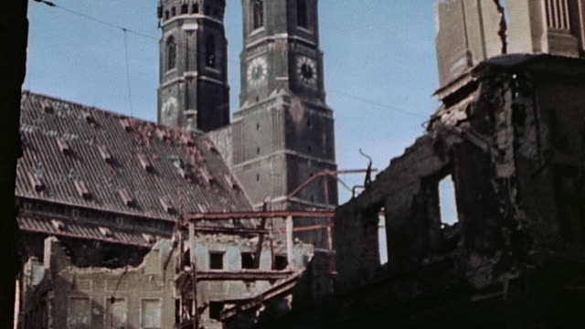 pedestrians walking past rubble with frauenkirche spires beyond / munich, germany - baviera video stock e b–roll