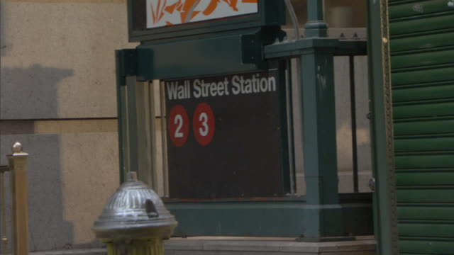 stockvideo's en b-roll-footage met ms pedestrians walking past wall street station sign / manhattan, new york, usa - wall street lower manhattan