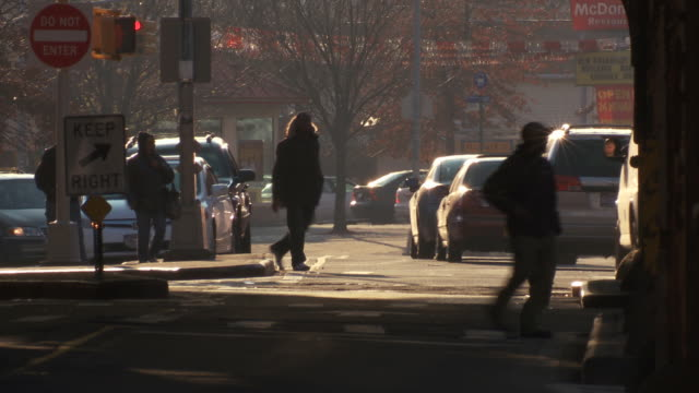Pedestrians walking through an Intersection as cars pass in the bronx during the day