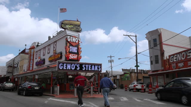 ws pedestrians walking through intersection and into geno's steaks restaurant with vehiclular traffic passing by / philadelphia, pennsylvania, united states - 2000 2010 stil bildbanksvideor och videomaterial från bakom kulisserna